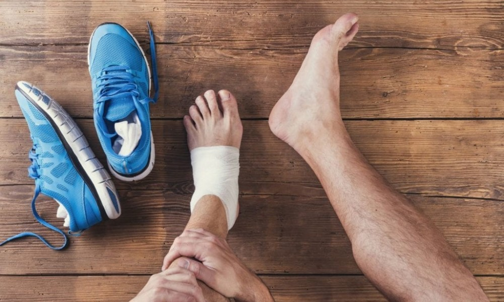 Mężczyzna trzyma się za lewą nogę. Obok leżą niebieskie, sportowe buty.
